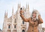 Woman taking selfies with digital camera while sightseeing Milan