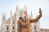 Woman traveler taking selfies with digital camera near Duomo
