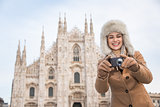 Happy woman tourist taking photos while sightseeing Milan