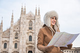 Smiling woman traveler with map looking aside near Duomo, Milan