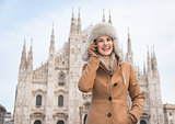Smiling woman tourist talking cell phone near Duomo, Milan