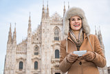 Happy woman writing sms on smartphone while standing near Duomo