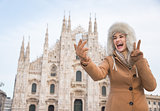 Woman tourist showing victory gesture and taking selfie in Milan