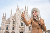 Smiling woman traveller taking selfie with smartphone in Milan