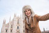 Happy woman tourist taking selfie in the front of Duomo, Milan