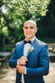 Groom in a blue suit buttoning cuffs