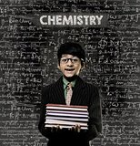 Chemistry. Genius Little Boy Holding Book Wearing Glasses