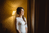 bride in a white dress standing near window