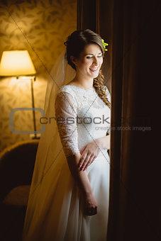 bride in a white dress standing near window