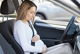Pregnant woman behind the steering wheel having contractions