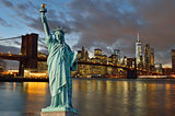Manhattah skyline with Brooklyn Bridge at night and Statue of Li