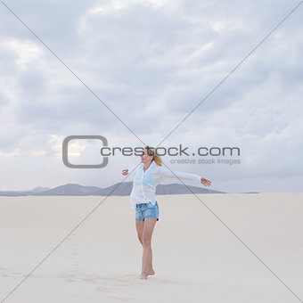 Carefree woman enjoying freedom on beach.