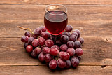 glass of wine or grape juice and fruit on wooden table
