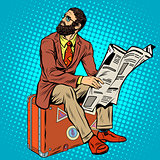 Bearded hipster traveler reading a newspaper