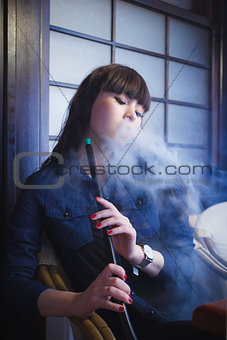 Beautiful young woman with hookah