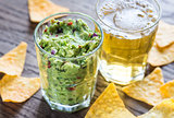 Guacamole with tortilla chips and glass of beer