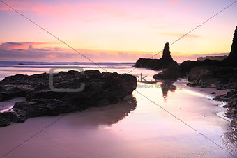Sunrise reflections in tidal wet sands Jones Beach Kiama