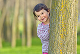 Little girl hiding behind a tree