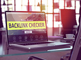 Backlink Checker on Laptop in Modern Workplace Background.