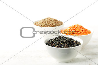 Bowls of assorted dried lentils with red lentils, black beluga l