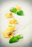 Homemade raw Italian tortellini and basil leaves