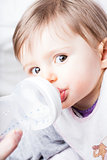 baby eating from her baby bottle