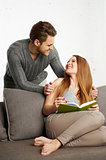 Happy young couple is relaxing on sofa in living room.