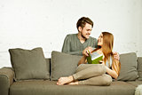 Smiling Romantic Couple With Book Talking on Couch