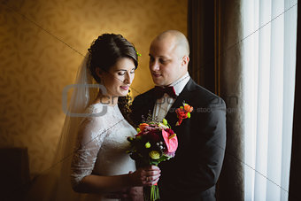 Bride and groom sitting at the window in room