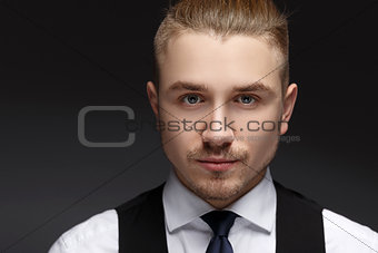 Close up portrait of a very handsome young man with grey eyes.