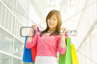Asian girl holding shopping bags
