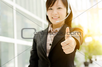 Asian female receptionist thumb up