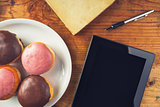 Delicious donuts and digital tablet computer on the table