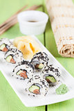 Uramaki sushi with avocado, raw salmon and black sesame