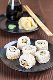 Uramaki sushi with carrot, cucumber, surimi and roasted white se