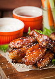 Hot chicken wings cooked with honey and soy,  topped with sesame