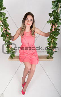 Beautiful young leggy blonde in a little pink dress and red high-heeled shoes sleeping on a swing, wooden swing suspended from a rope hemp, rope wrapped vine and ivy