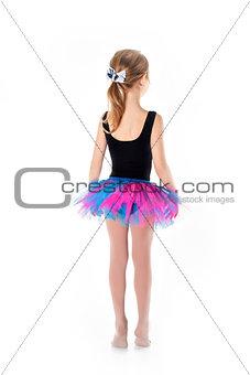 Little ballerina in purple skirt standing on white background