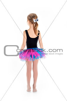 Little Ballerina in tutu on a white studio background. Studying dance is busy doing the exercises.