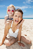 Smiling mother and daughter in swimsuits at sandy beach