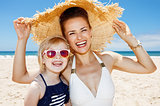 Smiling mother and daughter under big straw hat at sandy beach