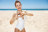 Happy woman in swimsuit showing heart shaped hands at sunny day