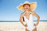 Happy woman in white swimsuit and straw hat at sandy beach