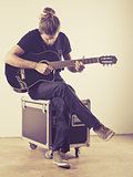 Young man sitting and playing guitar