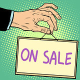 Hand holding a sign on sale