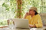 Pensive senior man with laptop