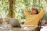 Senior man outdoors with laptop