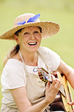 senior woman playing guitar outdoors
