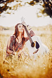 Portrait of lovely young hippie girl with guitar. Outdoor shot