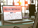 Social Network on Laptop in Modern Workplace Background.